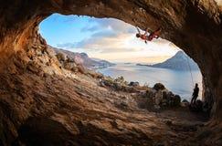 Ligação da jovem mulher que escala na caverna imagens de stock
