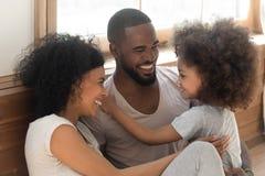 Ligação preta feliz da família que ri para sentar-se no assoalho do quarto foto de stock royalty free