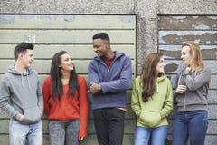 Liga av tonåringar som ut hänger i stads- miljö Arkivbild