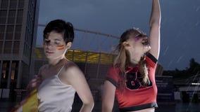 Liga de los campeones, dos fanáticos del fútbol de las chicas jóvenes en la lluvia, confrontación, España e Inglaterra, estadio e metrajes