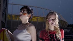 Liga de los campeones, dos fanáticos del fútbol de las chicas jóvenes en la lluvia, confrontación, España e Inglaterra, estadio e almacen de metraje de vídeo