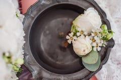 Liga del ` s del Boutonniere y de la novia en fondo del ramo del ` s de la novia Foto de archivo