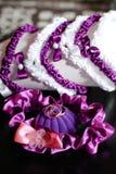Liga roxa da pétala da caixa com alianças de casamento Foto de Stock Royalty Free