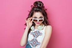 Ligando a la muchacha fresca de la moda bonita con los auriculares que llevan las gafas de sol blancas de la ropa colorida con mi Imagen de archivo libre de regalías