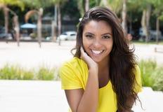 Ligar a la mujer latina en la camisa amarilla que mira la cámara Fotos de archivo libres de regalías