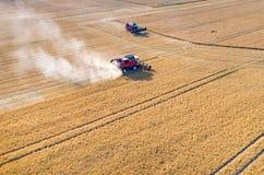 Ligas e tratores que trabalham no campo de trigo Fotografia de Stock