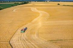 Ligas e tratores que trabalham no campo de trigo Fotografia de Stock Royalty Free
