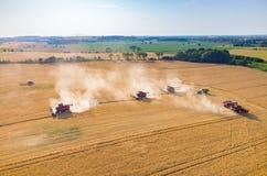 Ligas e tratores que trabalham no campo de trigo Fotos de Stock Royalty Free