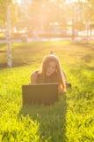 ligga för flickagräsbärbar dator arkivbild