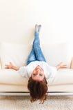 Ligga för kvinna som är uppochnervänt på en soffa Arkivbild