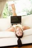 Ligga för kvinna som är uppochnervänt på sofaen genom att använda bärbar dator Arkivbild