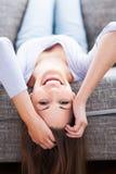 Ligga för kvinna som är uppochnervänt på soffan Fotografering för Bildbyråer