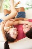 Ligga för par som är uppochnervänt på sofaen Arkivbilder