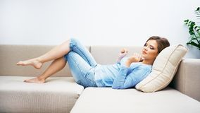 Ligga för soffa för ung kvinna royaltyfria bilder