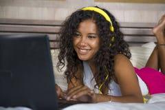 Ligga för sovrum för ung härlig lycklig svart latinamerikansk kvinna som hemmastatt är gladlynt på säng som lyssnar till internet arkivbilder