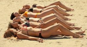 ligga för strandbikiniflickor som är sandigt flera Royaltyfria Foton