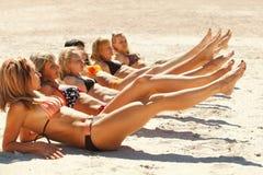 ligga för strandbikiniflickor som är sandigt flera royaltyfri fotografi