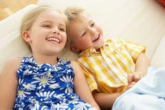 Ligga för två barn som är uppochnervänt på sofaen hemma Arkivfoton