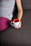 Ligga med koppen av tea Royaltyfri Foto