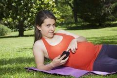 Ligga som är gravid med mobilen som ser kameran Royaltyfri Fotografi