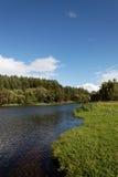 Liggande, äng, den blåa skyen och flod Royaltyfria Foton