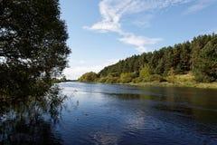 Liggande, äng, den blåa skyen och flod Fotografering för Bildbyråer