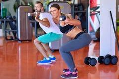 Liggande armhävning för styrka för idrottshallman- och kvinnaliggande armhävning med hanteln i en genomkörare Royaltyfri Fotografi