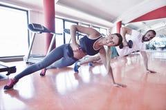 Liggande armhävning för styrka för idrottshallman- och kvinnaliggande armhävning med hanteln i en wor Royaltyfri Bild