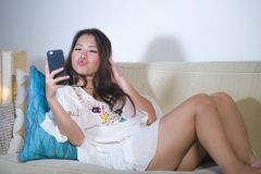 Liggande hemmastadd soffasoffa för härlig lycklig asiatisk koreansk kvinna genom att använda internet som daterar app i mobiltele arkivfoto