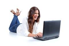 Liggande lyckligt bläddra för attraktiv kvinna i hennes bärbar dator Royaltyfri Bild
