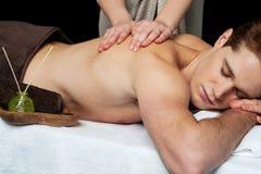 Liggande man som får en tillbaka massage arkivfoto