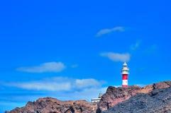 Liggande med rocks, skyen och fyren. Arkivbilder