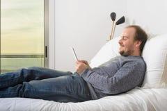 Liggande säng för man som ler hållande minnestavlasolnedgångsolnedgång till och med fönstret Arkivbild