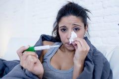Liggande sjuk hemmastadd soffa för ung attraktiv latinamerikansk kvinna i förkylning och influensa i magknipsjukdomtecken royaltyfri bild