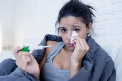 Liggande sjuk hemmastadd soffa för ung attraktiv latinamerikansk kvinna i förkylning och influensa i magknipsjukdomtecken arkivbild