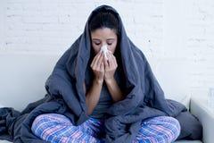 Liggande sjuk hemmastadd soffa för ung attraktiv latinamerikansk kvinna i förkylning och influensa i magknipsjukdomtecken royaltyfria foton