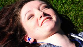 Liggande solbada för ung flicka under solen med hörlurar i öronen arkivfilmer