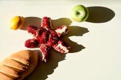 Liggen het brood lange brood en de rijpe rode sappige granaatappel, groene appel, gele citroen afzonderlijk op een witte achtergr royalty-vrije stock foto's