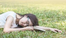 Liggend het grasgebied van de close-upvrouw nadat zij voor lezing in de middag vermoeide royalty-vrije stock afbeelding