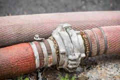 Ligger den röda slangar förbindelsekopplingen på trottoaren royaltyfria foton
