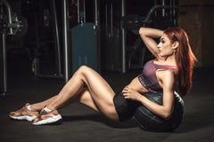 Ligger den sportiga unga flickan för härlig kondition på bollen som böjer buk- muskler Arkivfoto