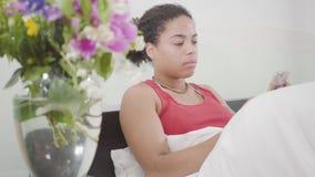 Ligger den unga nätta afrikanska amerikanen för ståenden som kvinnan precis vaknade upp, henne, i sängen som smsar på en mobiltel arkivfilmer