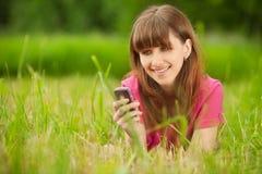 ligger det mobila telefonkvinnabarn Royaltyfri Foto