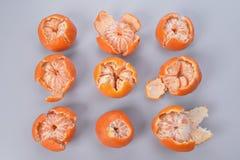 Ligger skalade och halva-skalade mandariner för apelsin lagt ut över en fyrkant på en grå bakgrund Royaltyfria Foton