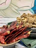 Ligger varm peppar för Bourgogne, på tabellen Torra Shiitakechampinjoner Bakgrund askfat royaltyfria foton