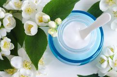 Ligh blue glass jar with facial cream/mask and jasmine blossom flowers background. Copy space. Ligh blue glass jar with facial cream/mask and jasmine blossom Royalty Free Stock Images