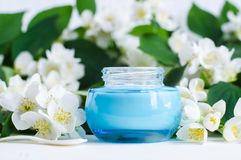 Ligh blue glass jar with facial cream/mask and jasmine blossom flowers background. Copy space Stock Photos