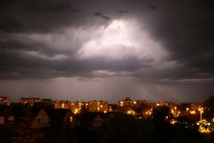 Lighning above dark clouds in thunderstorm stock photo