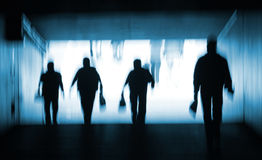 Into The Light. Abstract blur silhouette of people walking out of a dark tunnel into the light. Blue toning stock images