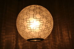 Light. Hanging globe shaped lamp against a brown background Royalty Free Stock Photo